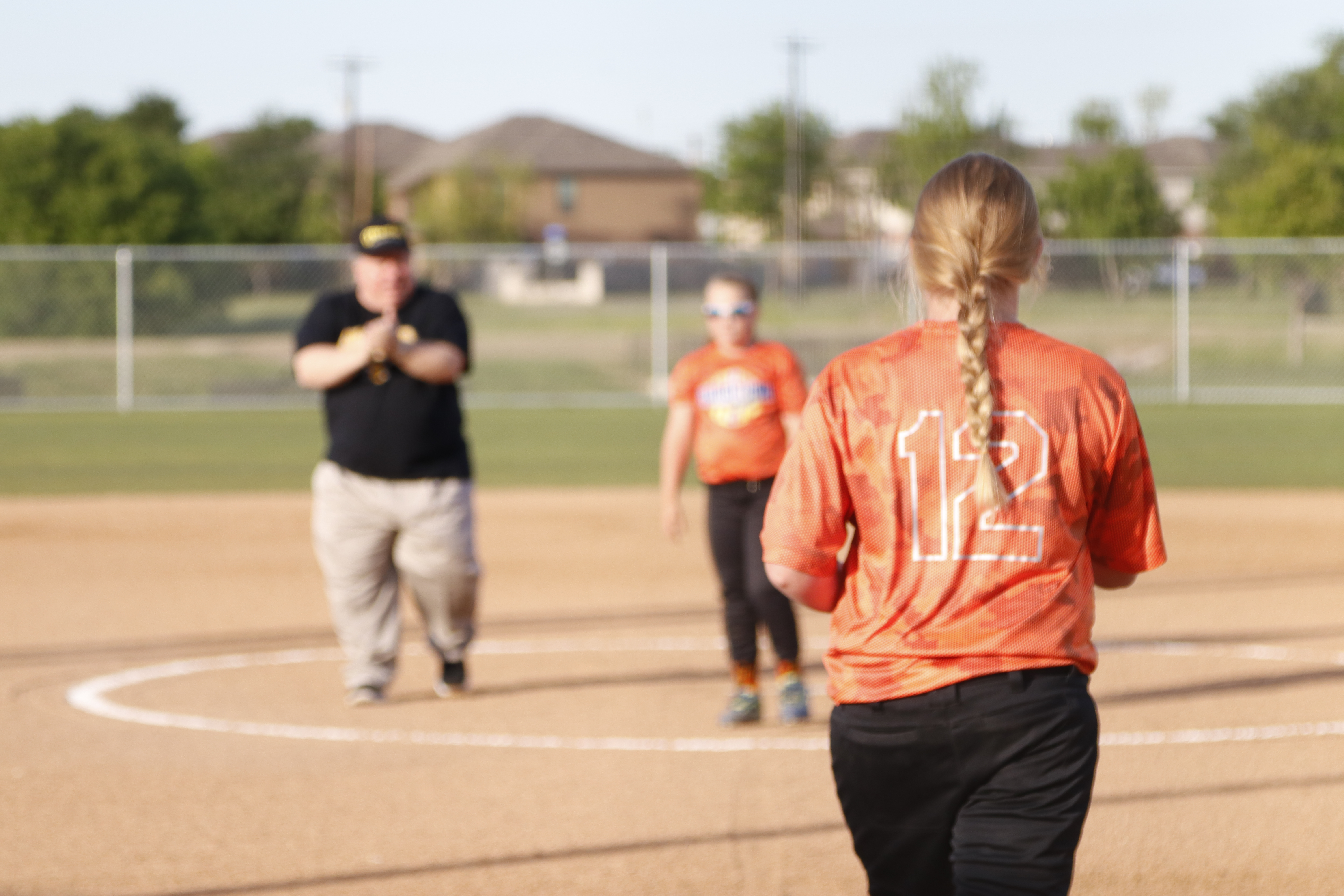 Two female softball players with the Mayor after throwing out the first pitch at VFW Park in Georgetown, TX