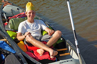 Boy in a kayak, barefoot wearing a yellow hat