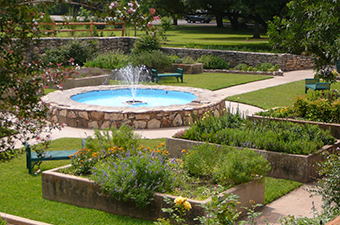 The Sunken Garden in Georgetown, TX has a round water fountain surrounded by garden boxes with blooming flowers.