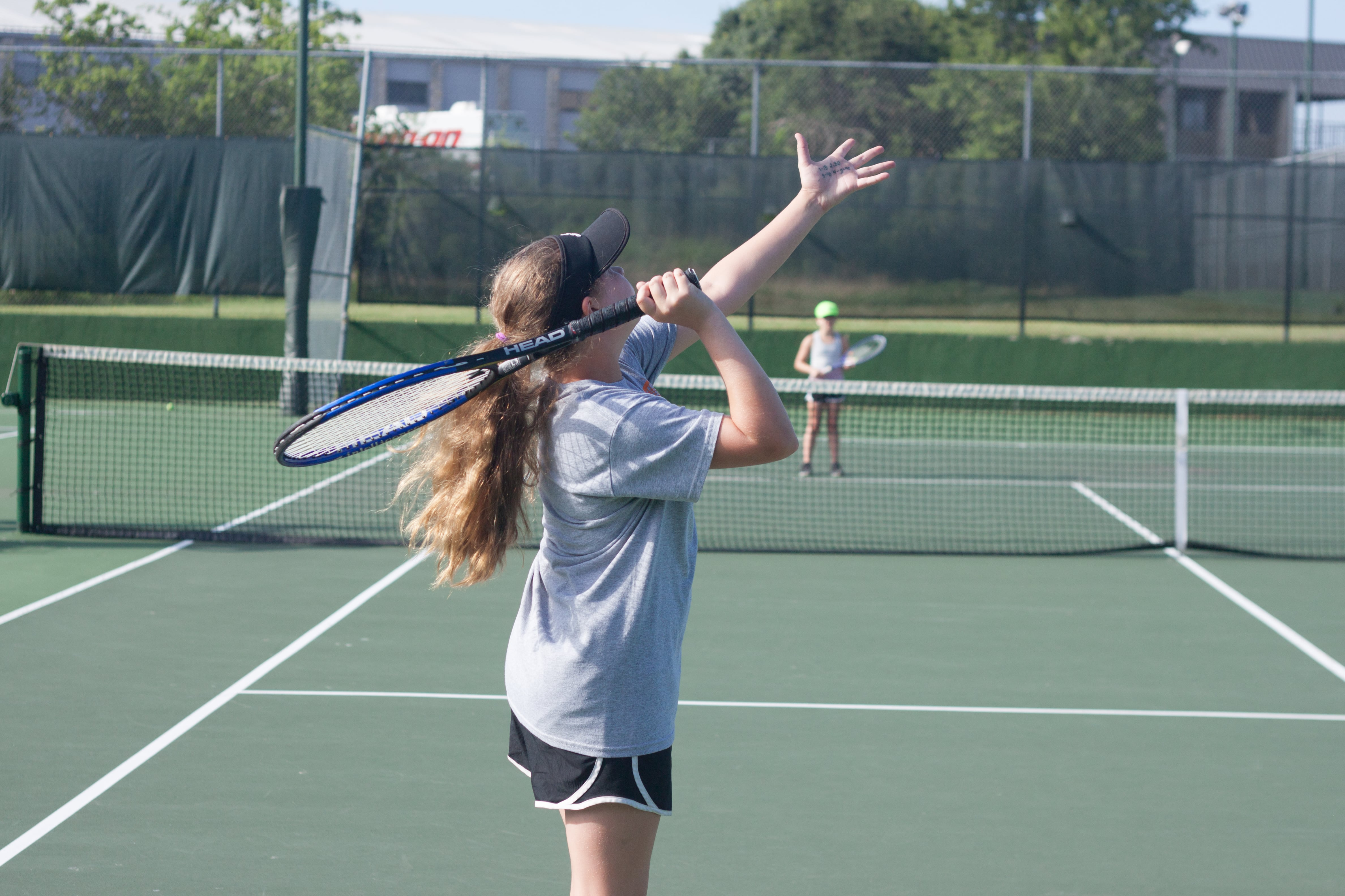 Girls playing tennis. Girl in the foreground is tossing the tennis ball into the air to prepare to serve.