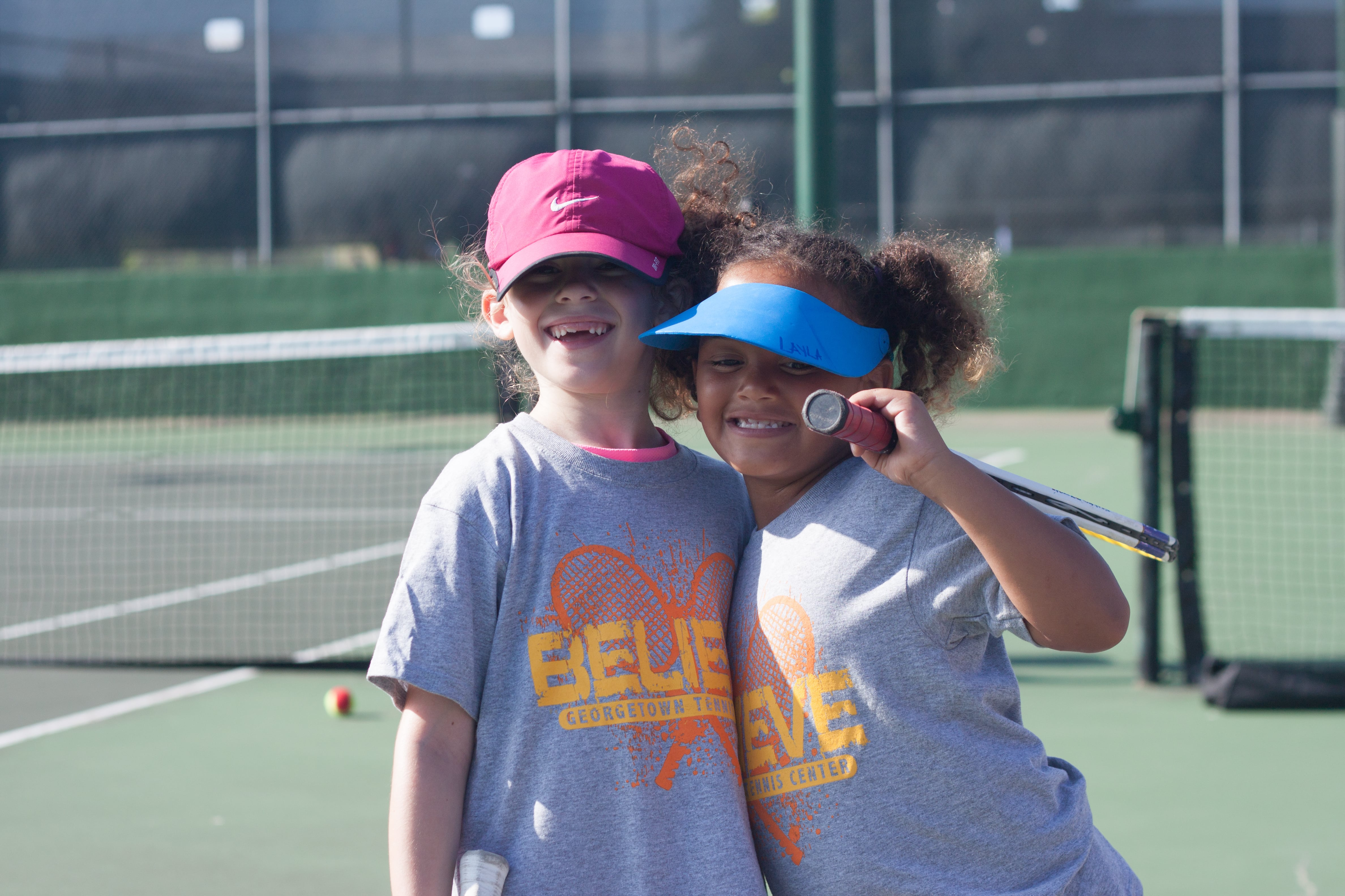 Two young girls wearing Believe Georgetown Tennis shirts smile while holding tennis racquets on the courts