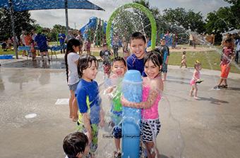 Children playing in the splash pad at San Jose Park in Georgetown, TX