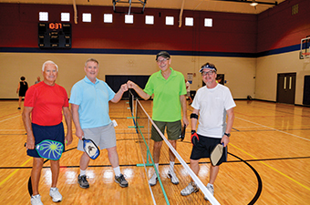 Men gathered at the pickleball net. The two men in the middle are giving each other knuckles and all four men are holding pickleball racquets.