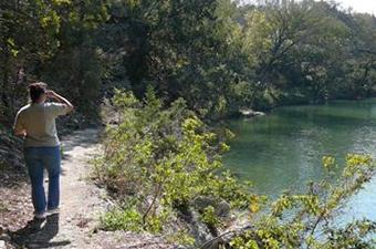 A woman hiking along the San Gabriel River in Georgetown, TX