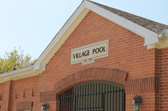 Village Pool Entrance in Georgetown, TX. A red brick building with a black iron gate and a sign that reads Village Pool.