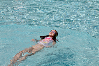 A girl floats on her back in a swimming pool