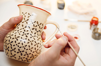 Person's hands painting a brown pattern on an off-white pot with a handle.