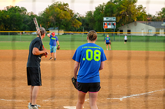Adults playing a softball game. A man is at home plate preparing to bat, and the pitcher is about to throw the ball.