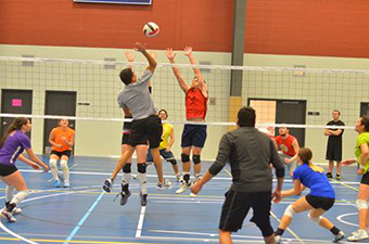 Adult volleyball game inside a gymnasium