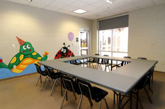 Event Room at the Georgetown Recreation Center. Tables and chairs are set in the middle of the room. A mural with a turtle and a ladybug are painted on the wall.