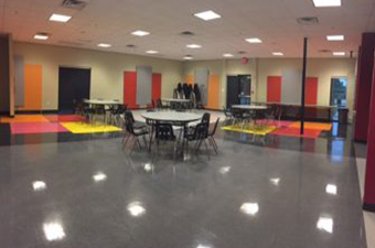 Teen 2 Room at the Georgetown Recreation Center has tables and chairs, with brightly colored flooring and walls.