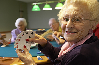 Group of senior citizens playing Bridge. Woman is showing her cards while smiling at the camera.