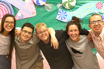 Five people pose for a photo in front of a Candyland-themed photobooth