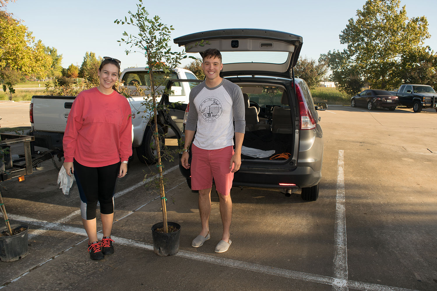 A man and a woman pose with a tree in front of their car that they received at the Arbor Day Tree Giveaway event in Georgetown, TX