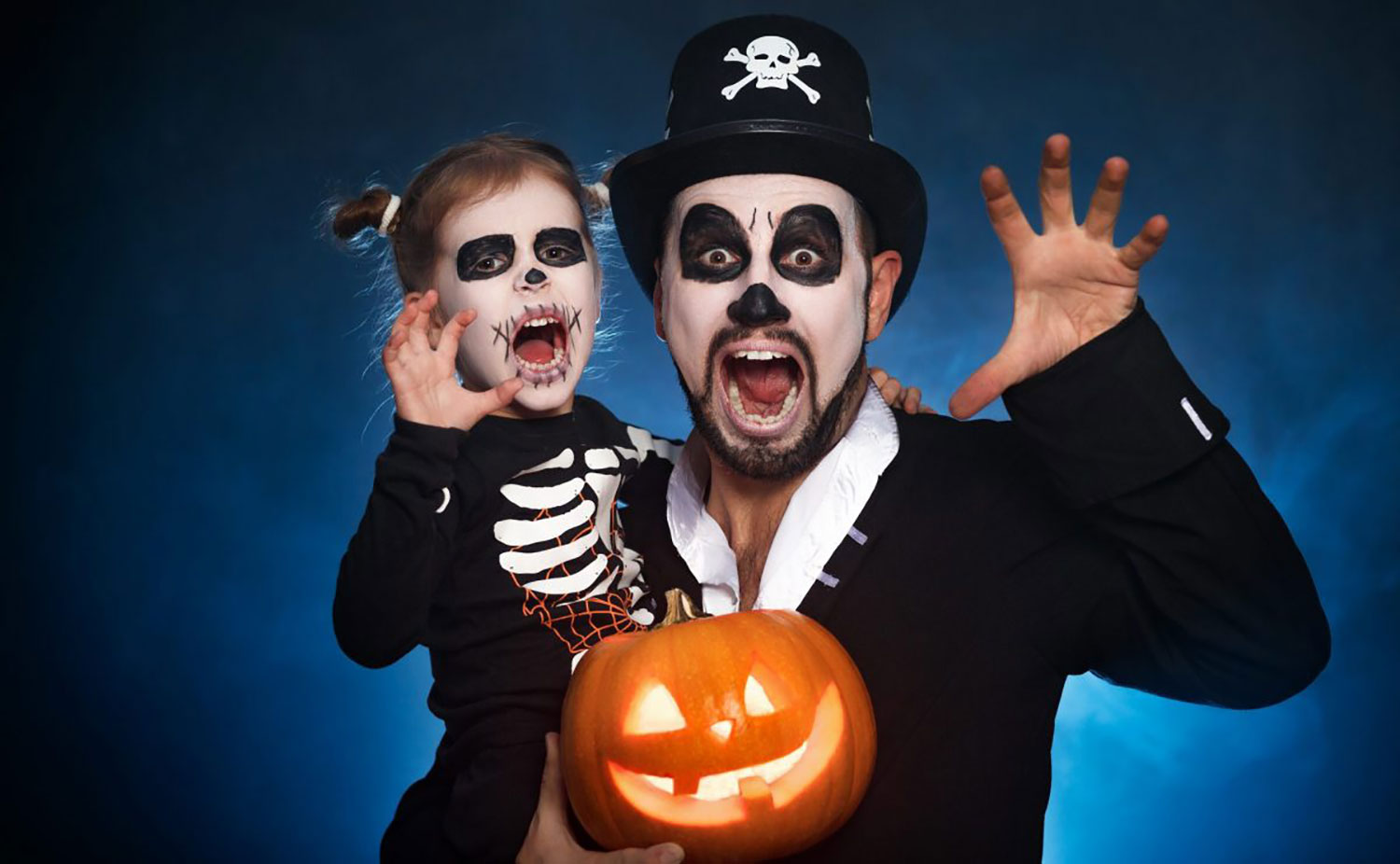 Girl and father dressed as skeletons for Halloween and holding a jack o lantern