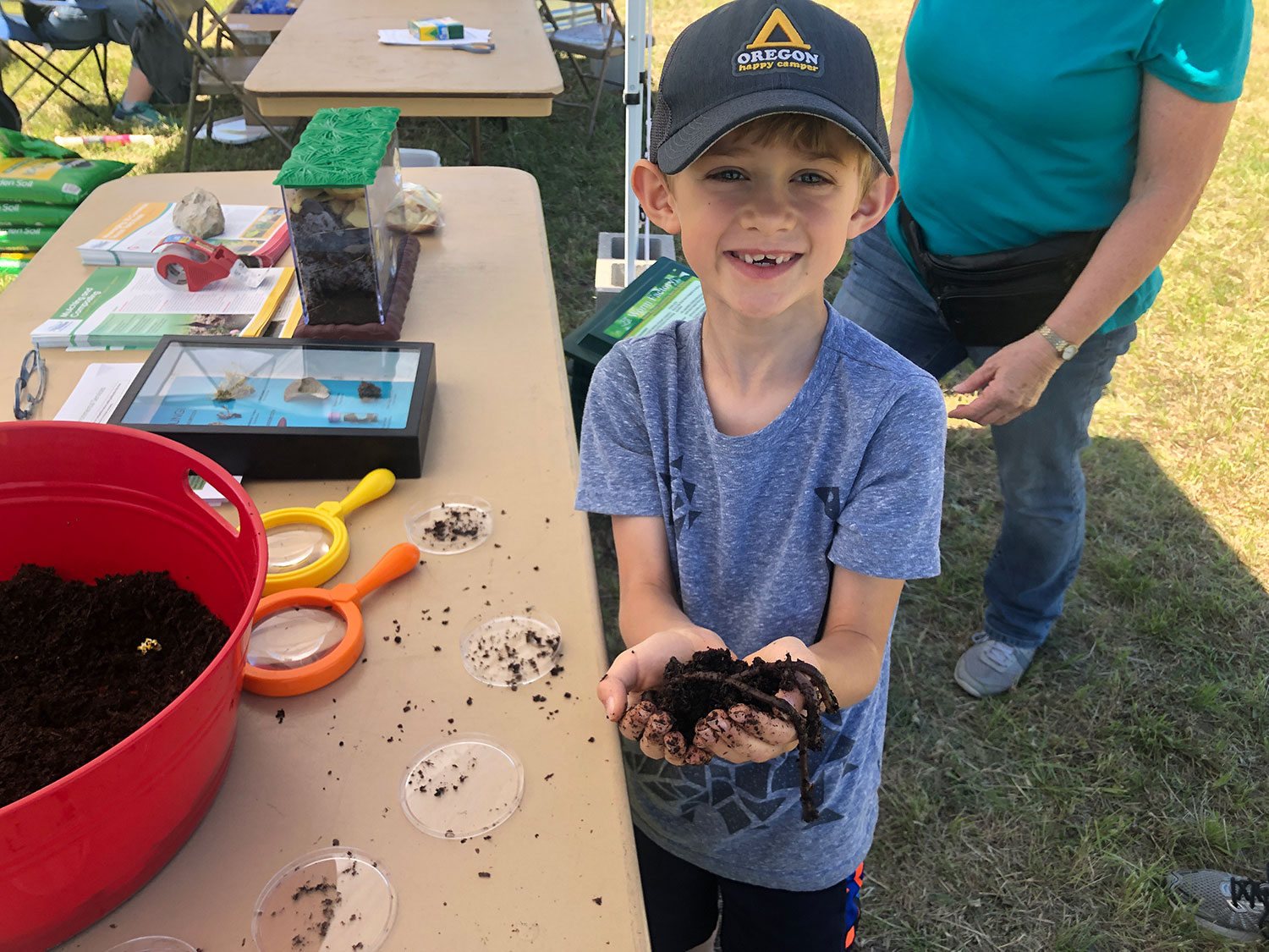 Boy wearing a hat and holding worms at a booth at Family Nature Fest at Garey Park