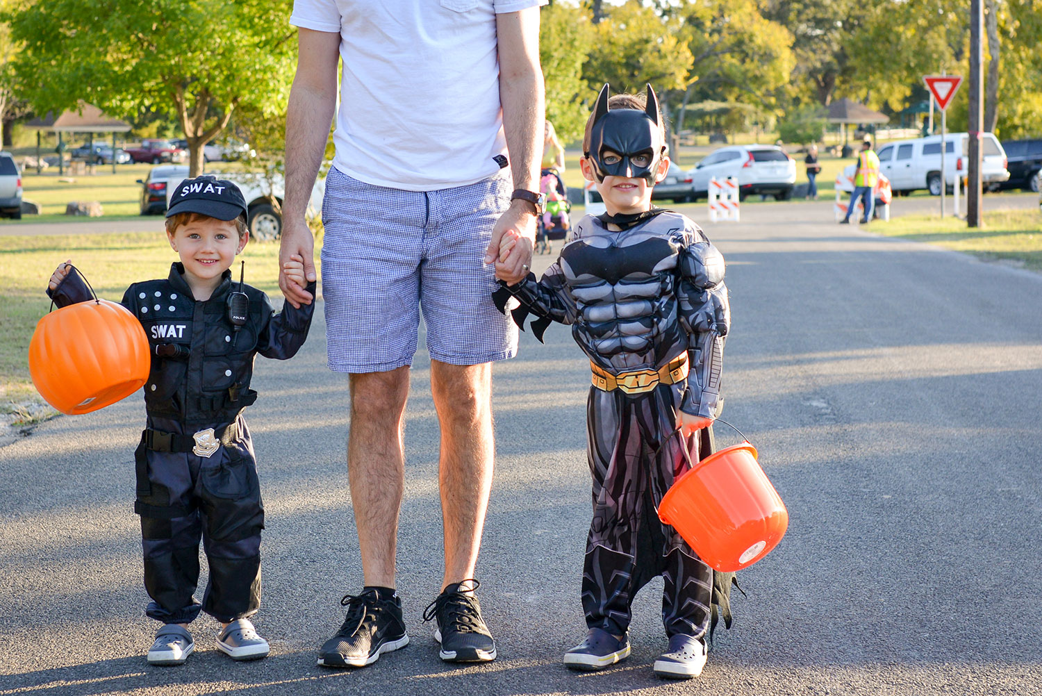 Two boys dressed in Halloween costumes holding their dad's hand and orange pumpkin buckets