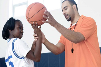 Athletic trainer holds a basketball while training a young woman