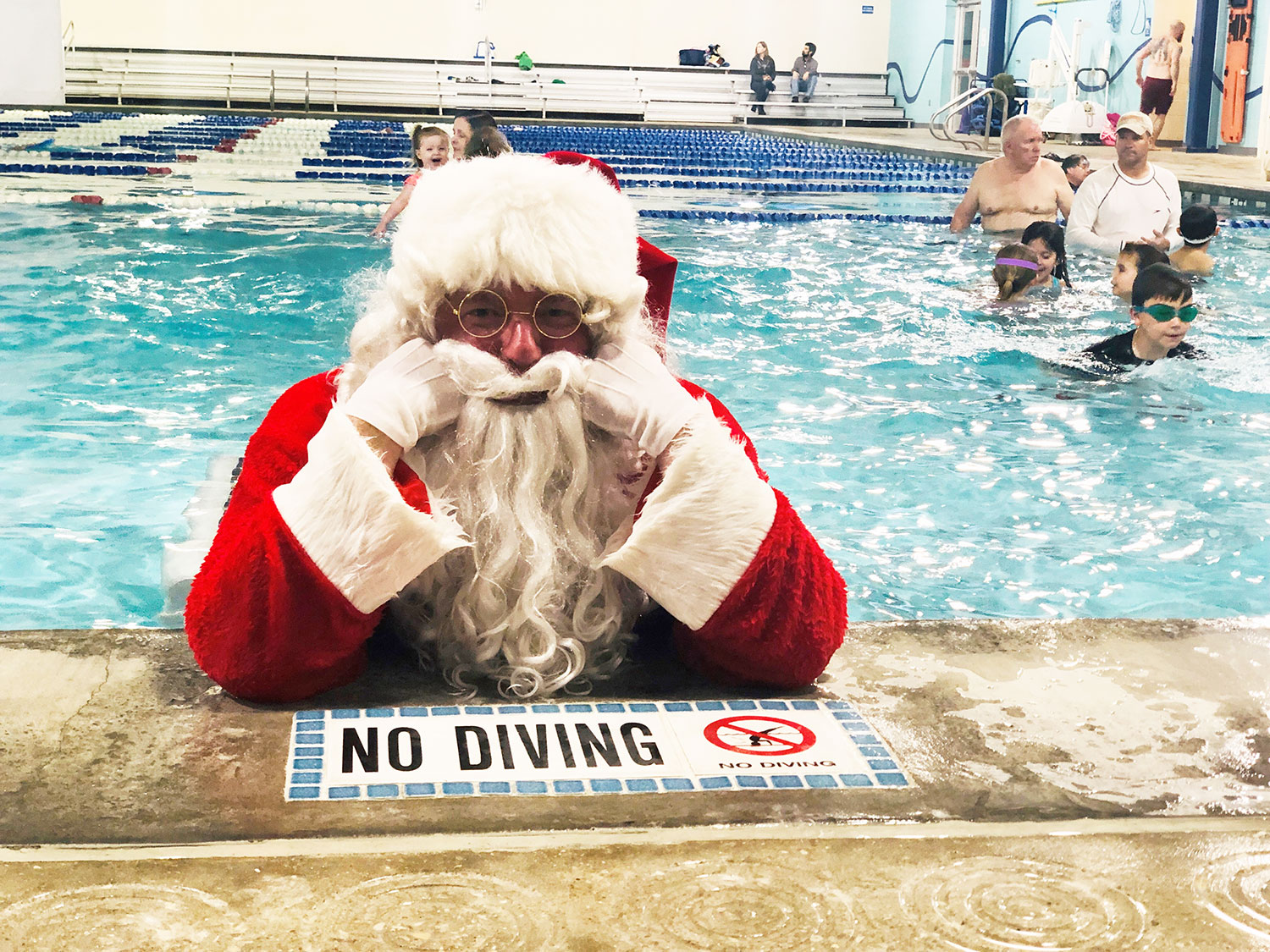 Santa poses on the edge of the pool