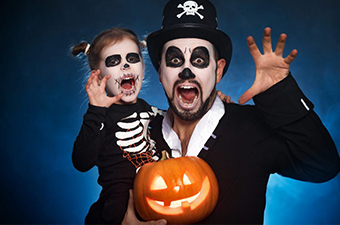 Girl and her father dressed as skeletons for Halloween and holding a jack o lantern