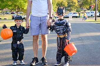 Two boys dressed up in Halloween costumes holding their father's hand and holding an orange pumpkin bucket in the other hand