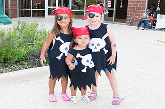 Three girls dressed in pirate costumes at the Pirate Party in Georgetown, TX