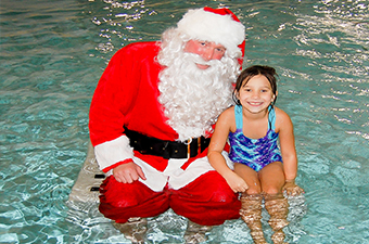 Girl poses for a photo with Santa in a swimming pool in Georgetown, TX