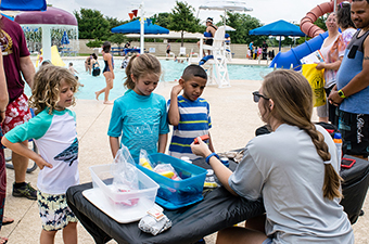 Woman showing a group of three kids water safety items during Water Safety Day in Georgetown, TX