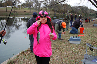 Girl wearing a pink jacket and hat holding trout she caught on the banks of the San Gabriel River in Georgetown, TX