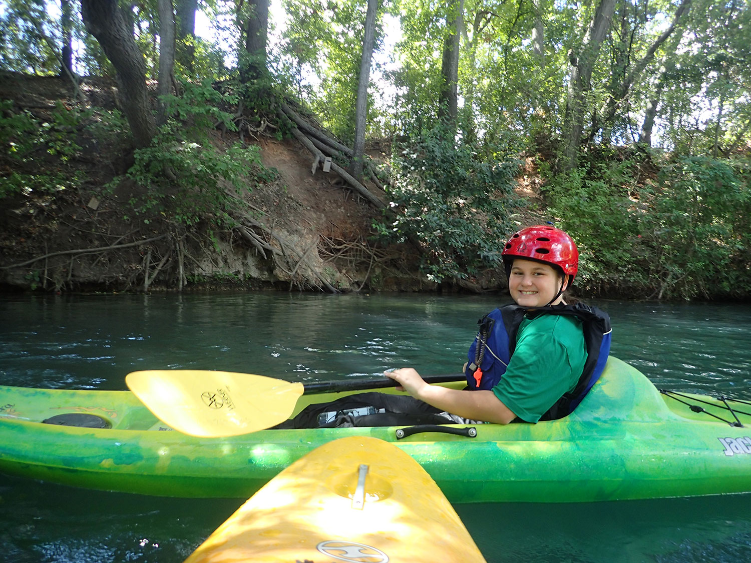 boy smiling while holding a yellow paddle wearing a red helmet while sitting in a green kayak