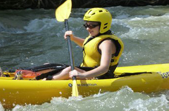 Woman wearing a yellow helmet while paddling a yellow kayak in whitewater