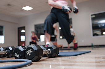 Women exercising while holding weights at a Boot Camp class at the Georgetown Recreation Center in Georgetown, TX