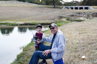 Man and child posing with fishing gear next to the Upper Pond at Garey Park