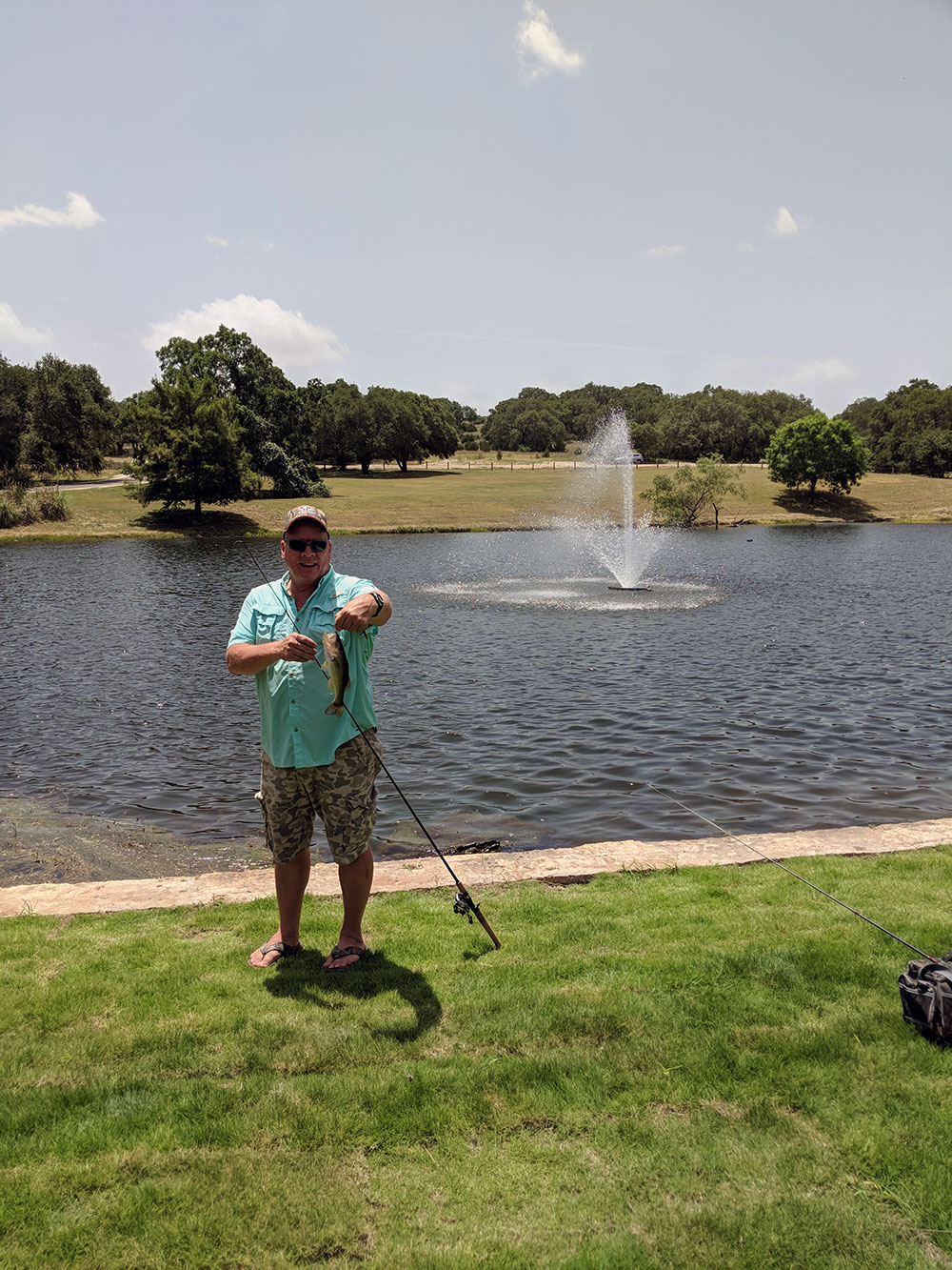 Fisherman holding a fish at the Upper Pond at Garey Park in Georgetown, tX