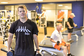 Man holding dumbbells in the fitness room at the Georgetown Recreation Center. Two other men are working out with dumbbells in the background.