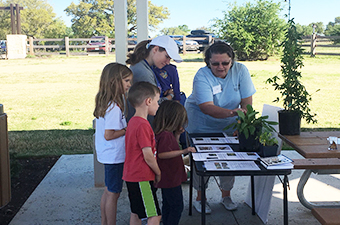Good Water Master Naturalist member leading a family in a youth outdoor program at Garey Park in Georgetown, TX