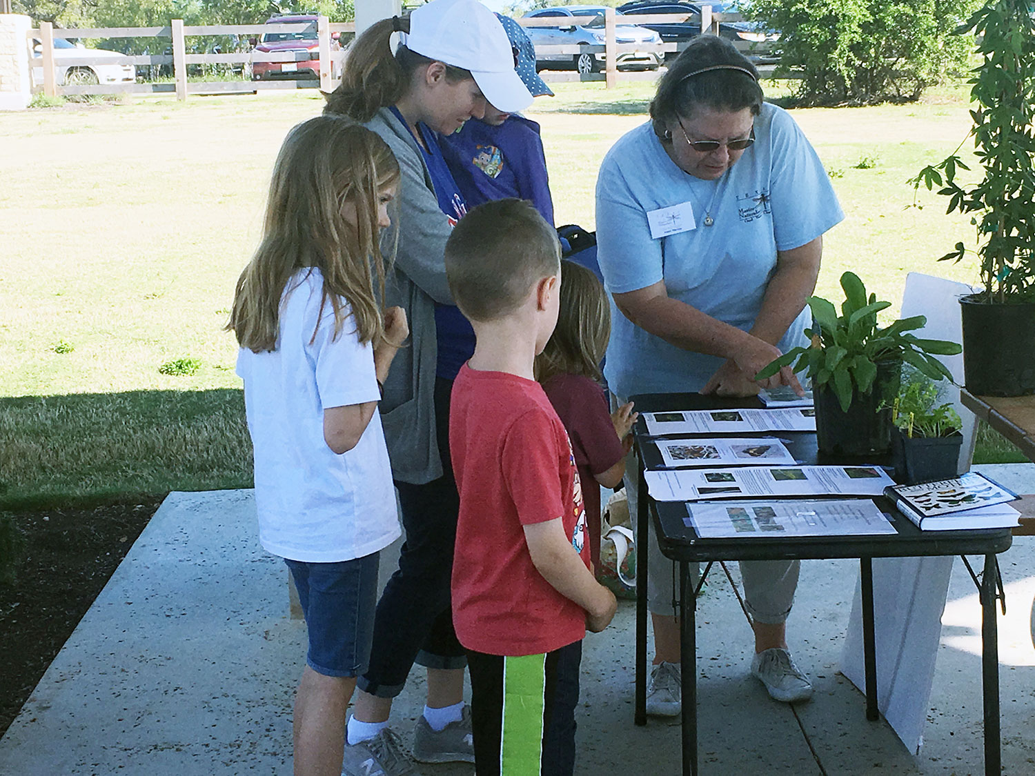 A representative from the Good Water Master Naturalists showing a family a program at Garey Park