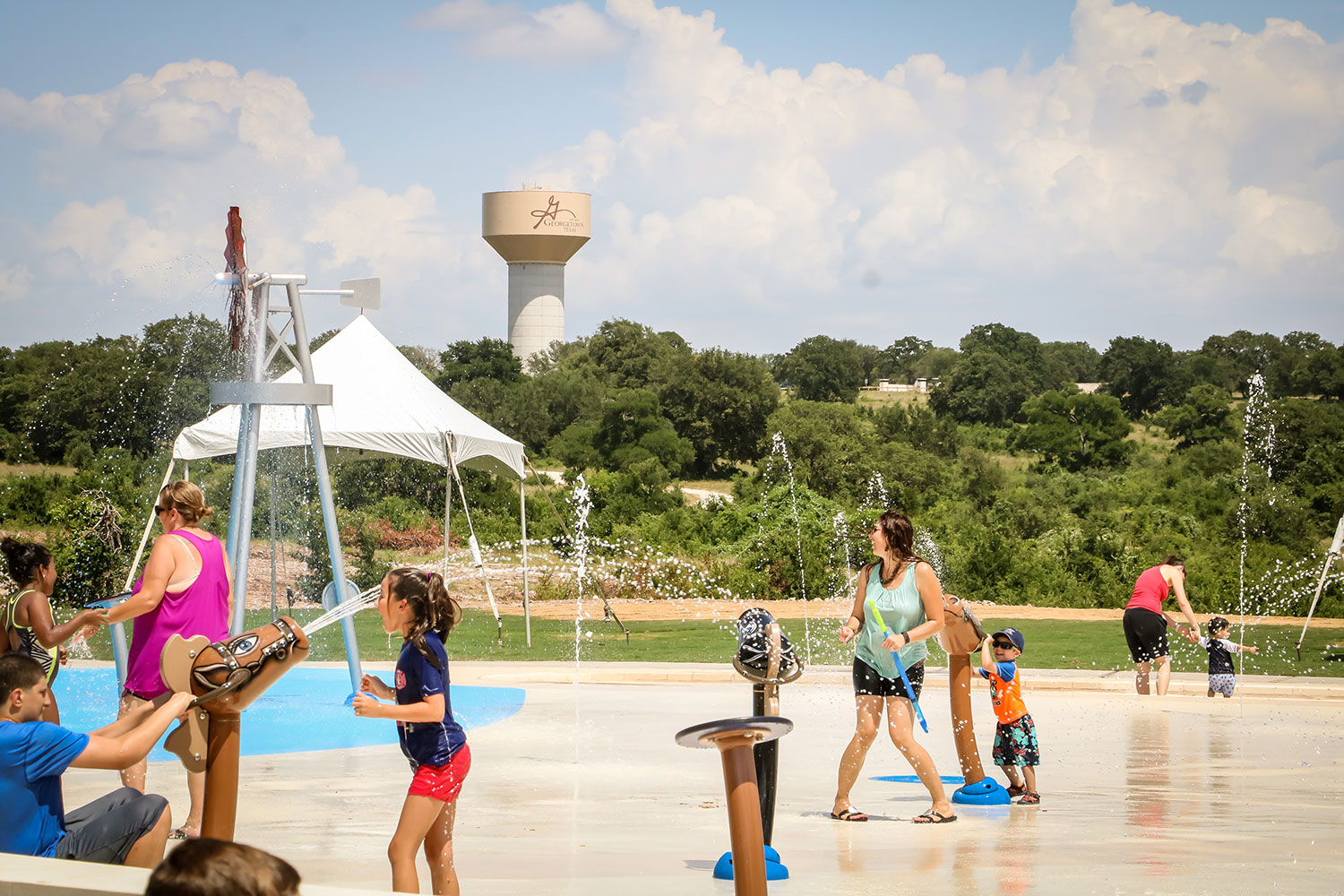 Families playing at the splash pad at Garey Park in Georgetown, TX