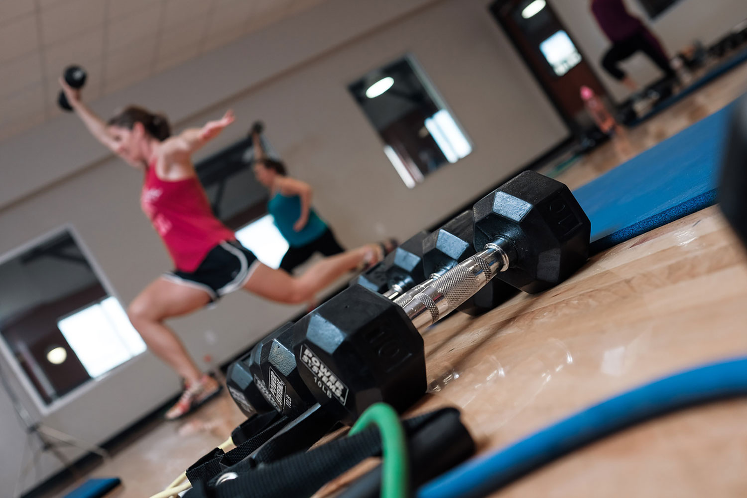 Women holding hand weights while taking a fitness class with weights and mats on the floor