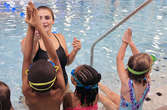 Lifeguard teaches group of three children.