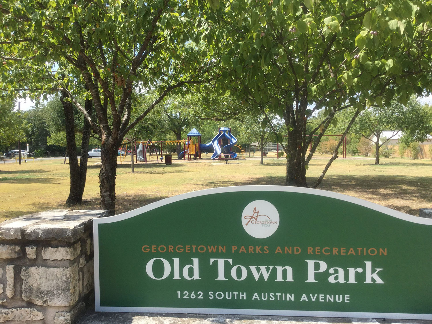 Entrance sign for Old Town Park in Georgetown, TX with playscape in the background