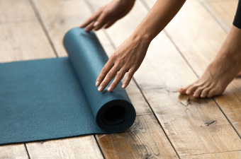 Woman rolling out yoga mat onto wooden floor. Close up on feet and hands.