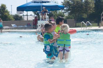 Children wearing green life jackets while swimming at the Outdoor Pool at the Georgetown Recreation Center