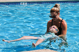 Lifeguard holds a girl while teaching her to float in the swimming pool
