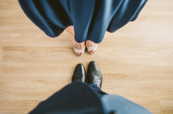 View of shoes from above. Woman's shoes are on top. She is wearing a blue dress with beige sandals. The man is below wearing a black jacket and black dress shoes.