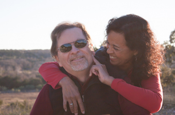 Woman has her arm around the man and is tapping his cheek while smiling at him.