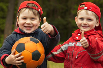 Two boys wearing red hats backwards while giving a thumbs up. The boy on the left is holding a soccer ball.