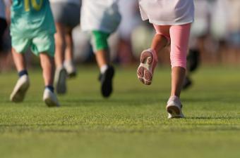 Group of kids running on a grass field