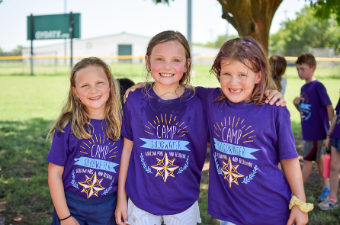 Three young girl pose in Camp Goodwater shirts during Camp Goodwater Camp in Georgetown, TX