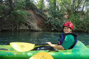 boy wearing a red helmet and paddling in a green kayak